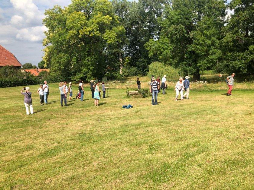 Eine Gruppe von 20 Menschen verteilt sich auf einer grünen Wiese