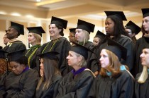 Students stand during the conferring of degrees portion of Saturday's undergraduate and graduate commencement services