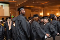 Christopher Carpenter, left, looks back to the crowd as students file into the First Baptist Church banquet hall for the undergraduate and graduate commencement services Saturday.