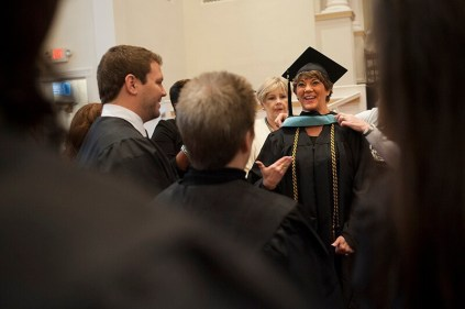 Kimberly Barnett laughs as her hood is adjusted in the sanctuary of the First Baptist Church in Gainesville before the start of the undergraduate and graduate commencement services Saturday.