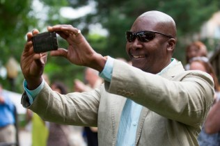 Robert Vil takes a video as his daughter Cassandra Carmel Vil-WIlson receives her diploma during this year's Women's College commencement ceremony.