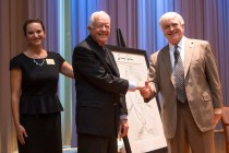 Former President Jimmy Carter poses for a photo with Brenau University President Ed Schrader and the university galleries director Nichole Rawlings.
