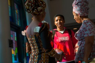 Mary Achebo, a Brenau freshman, speaks with fellow Nigerians as the women of the QBWA set up booths in the Burd Center.