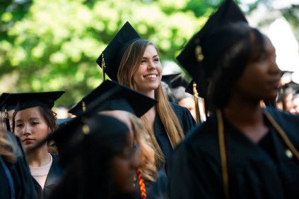 Rachel Adam smiles as she and her fellow graduating seniors sit during the 2015 Brenau Women's College Commencement.