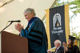 Brenau University President Ed Schrader applauds after conferring degrees upon the 2015 Women's College graduates.