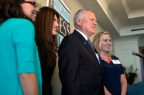 Brenau occupational therapy alumnae Allison Guisasola, Rachel Strazynski Shusner, and Shelby Wrenn pose for a photo with Gov. Nathan Deal at the Atlanta Press Club lunch where deal signed House Bill 62 into law. HB 62 which helps special needs children of military personnel started as a class project the students were involved in as they earned their masters degrees.