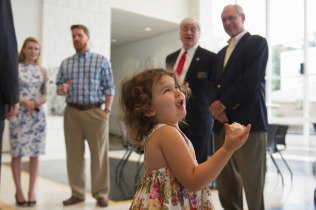 Coco Cleveland laughs while eating a sweet during the celebration to honor the dedication of The Cleveland Physical Therapy Lobby at the Brenau Downtown Center on Friday, July 3, 2015, in Gainesville, Georgia. (AJ Reynolds for Brenau University)