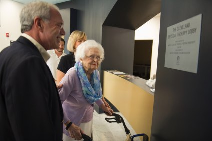 John R. Cleveland, left, shows his mother Mary Cleveland a plaque honoring her and her late husband Ralph Cleveland during the celebration to honor the dedication of The Cleveland Physical Therapy Lobby at the Brenau Downtown Center on Friday, July 3, 2015, in Gainesville, Georgia. (AJ Reynolds for Brenau University)