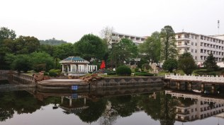 The beauty of Anhui Normal University's old campus is on display in this photo of the garden and lake area on campus. It was a common sight to see students relaxing and studying in this beautiful space. To the right, several men's dormitories can be seen, while the hill and tower in the middle background are a part of Zheshan Park next to the historic campus.