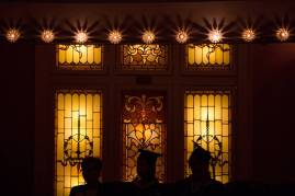 Students and Provost Nancy Krippel, left, are silhouetted in front of the windows of the Pearce Auditorium during the Brenau University College of Health Sciences Graduate Hooding Ceremony on Thursday, May 5, 2016. (AJ Reynolds/Brenau University)