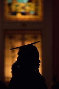 A graduating student walks past a stained glass window in Pearce Auditorium before The Women's College Commencement on Friday, May 6, 2016, in Gainesville, Ga. (AJ Reynolds/Brenau University)