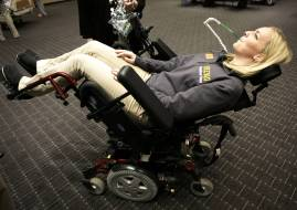 """Brenau University occupational therapy graduate student Lauren Tomy discovers how lean back a """"Sip & Puff Power Wheelchair"""" by blowing on a straw. (Phil Skinner for Brenau University)"""