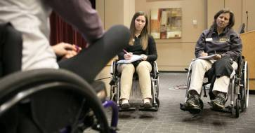 Brenau University occupational therapy graduate students Becca Fiscal, right, and Rachel Adams learn how to put on shorts while in a wheelchair from former Shepherd Center patient Ally Poole. Poole returned just one month after a seven-week stay at the Shepherd Center to help the Brenau students. (Phil Skinner for Brenau University)