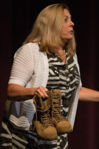 Patricia Wolfe pulls out a pair of combat boots during her speech during the 4th Annual Women's Leadership Colloquium on Friday, March 17, 2017. (AJ Reynolds/Brenau University)