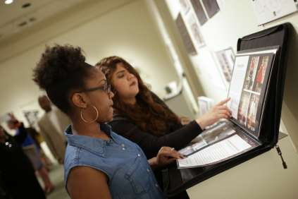 Kiah Hinds, 2018, and Genesis Sanchez, 2017, flip through work by Rachelle Nicole Brown during the 2017 Alumnae Reunion Weekend at Brenau University, Saturday, April 08, 2017. (Photo/ John Roark for Brenau University)