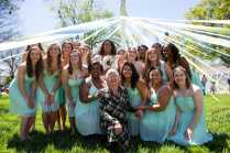 The May Court with Sara Hubaishi and Debbie Thompson stand underneath the wrapped maypole. (AJ Reynolds/Brenau University)