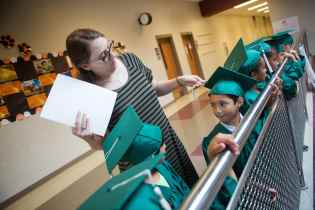 Olivia McFerrin fixes a students cap during the commencement ceremony for the RISE Program on Friday, July 14, 2017 at Fair Street School. (AJ Reynolds/Brenau University)