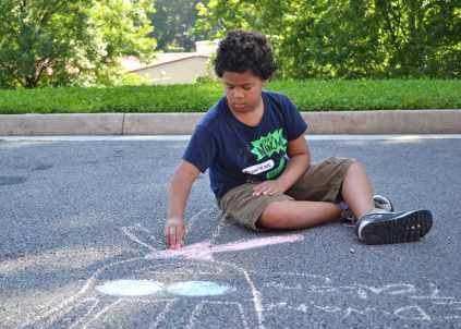 Aidan Duckworth draws with chalk at Fair Street International Academy in Gainesville during the RISE Summer Program. The program is a parternship between community partners including Brenau University.