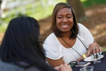 Jennifer Perrimon, WC '08 & BU '14, chats with a friend during the Reunion on the Lawn. (AJ Reynolds/Brenau University)