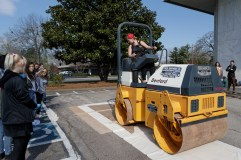 Claudia Wilburn drives the steamroller at the Colossal Prints printmaking workshop at Brenau University on Friday, March 23, 2018.