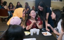 "ANU-Brenau University student Jie ""Lily"" Li, center, reacts as she shows a photograph on her phone to Brenau University student Razia Hussaini, left, and ANU-Brenau University student Jingjing ""Jocelyn"" Heng (standing) during a luncheon at Brenau University Friday May 4, 2018 in Gainesville, Ga. (Jason Getz for Brenau University)"