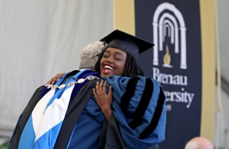 Kenya Hunter hugs Brenau University President Ed Schrader after she received her diploma during the Women's College Commencement at Brenau University Friday May 4, 2018 in Gainesville, Ga. (Jason Getz for Brenau University)