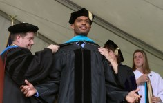 Brenau University Provost James Eck, left, and Chair of the Physical Therapy Department Kathye Light fixes the academic regalia of Israel Branford as he receives his doctorate in physical therapy during the graduate and undergraduate commencement Saturday May 5, 2018 in Gainesville, Ga. (Jason Getz for Brenau University)