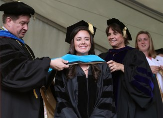 Brenau University Provost James Eck, left, and Chair of the Physical Therapy Department Kathye Light fixes the academic regalia of Sarah Gay as she receives her doctorate in physical therapy during the graduate and undergraduate commencement Saturday May 5, 2018 in Gainesville, Ga. (Jason Getz for Brenau University)