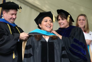 Brenau University Provost James Eck, left, and Chair of the Physical Therapy Department Kathye Light fixes the academic regalia of Amy Tice as she receives her doctorate in physical therapy during the graduate and undergraduate commencement Saturday May 5, 2018 in Gainesville, Ga. (Jason Getz for Brenau University)