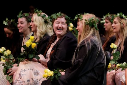 Seniors laugh on stage during a class day performance. (AJ Reynolds/Brenau University)