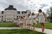 Junior students carry the daisy chain toward the Crow's Nest for Class Day. (AJ Reynolds/Brenau University)