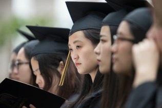 "Xin Yan ""Daisy"" Qiu (center) looks up from her diploma during the 2018 Spring Commencement Ceremony on Saturday, May 5, on Brenau University's historic Gainesville campus. (Nick Bowman for Brenau University)"
