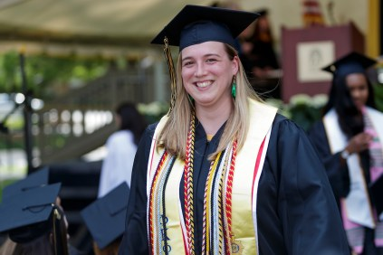 Young woman in graduation regalia walks away from stage smiling
