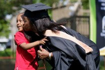 Aquarium Williams in graduation regalia kisses child on the cheek
