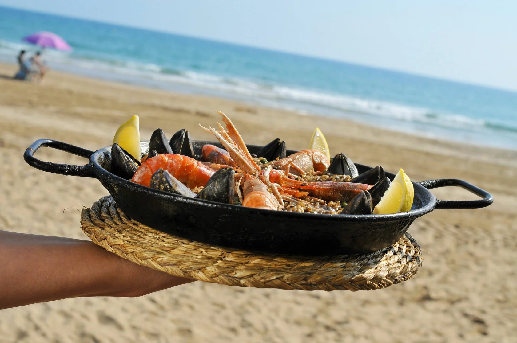 32139727 - a typical spanish paella with seafood in a paellera, the paella pan, on the beach
