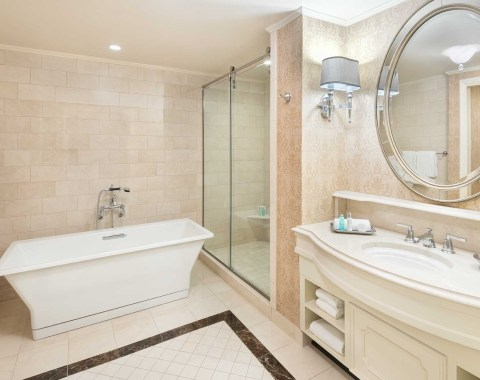 Bright luxury bathroom in the Presidential Suite at Windsor Court Hotel, featuring Italian marble and separate shower and tub