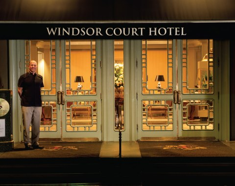 View of the entry to Windsor Court Hotel including doorman and a glimpse into the lobby of the luxry New Orleans hotel