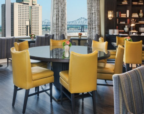 Club Level features yellow leather chairs, dark wood finishes and skyline views of New Orleans
