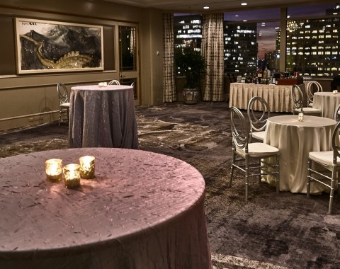 An evening event in La La Chinoiserie at Windsor Court Hotel, with a few candlelit tables and a view of New Orleans