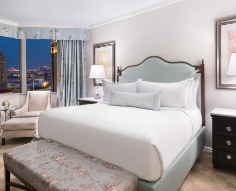 A luxury suite at Windsor Court Hotel, featuring a queen size bed, night stand with lamp, and nighttime view of New Orleans