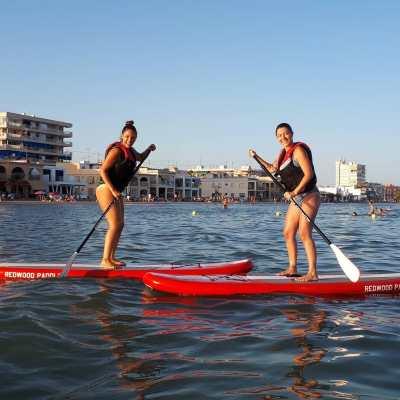 Dos mujeres aprendiendo paddle surf en playa lisa. santa pola