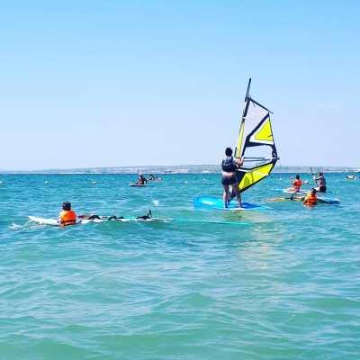 Personas practicando distintos deportes en el mar