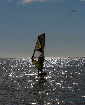Figura de un hombre detrás de una vela de windsurf, mientras navega
