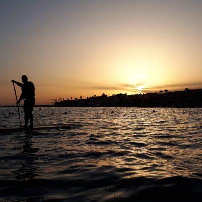 Hombre haciendo paddle surf al atardecer en Santa Pola