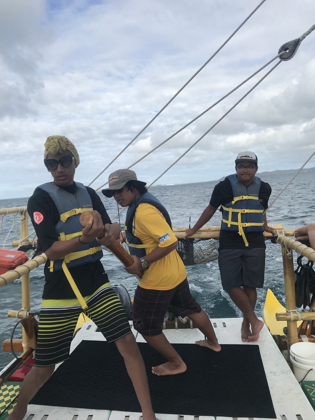 students on a sailing ship working the rudder on the ocean