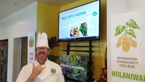 """Chef Dan in the Uala Leaf Cafe in chef hat and chef's coat. He is giving a shaka. Tv monitor behind him with an image of food and reads """"Meals with a Mission""""."""