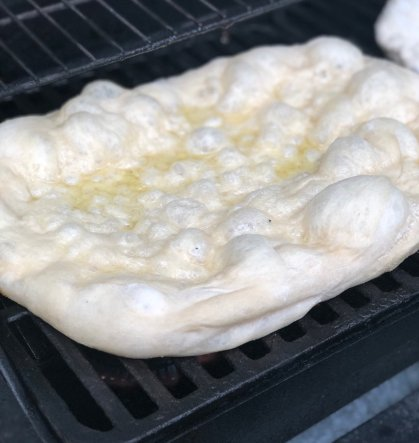 Pizza dough that's been stretched into a rectangle shape and placed on the gas grill grates. It's puffed up and you can see it's been rubbed with olive oil.