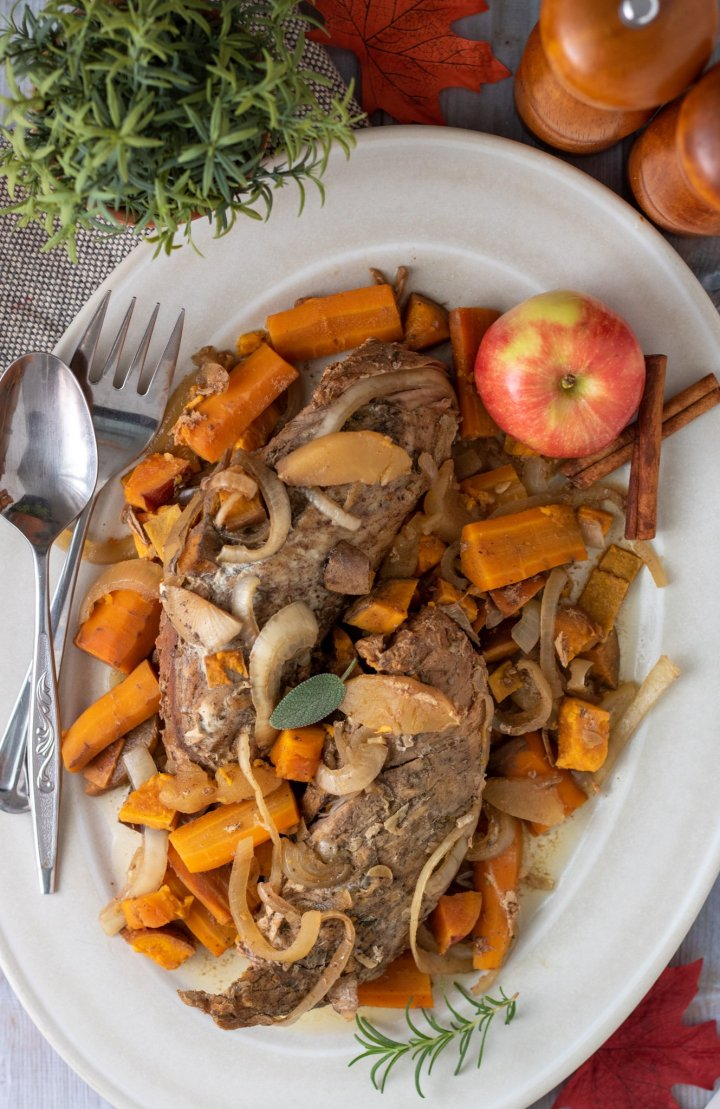A large oval serving platter with apple cider pork tenderloin on top of carrots, onions and sweet potatoes.  There's a red apple on the serving platter and two silver serving utensils.  There's a small fresh rosemary plant in the background