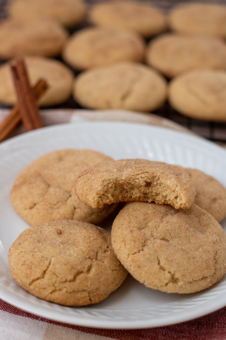 A small round white plate with 5 chai spice snickerdoodle cookies. The top cookie has a bite taken out of it. There's two cinnamon sticks with cooling rack of more cookies in the background