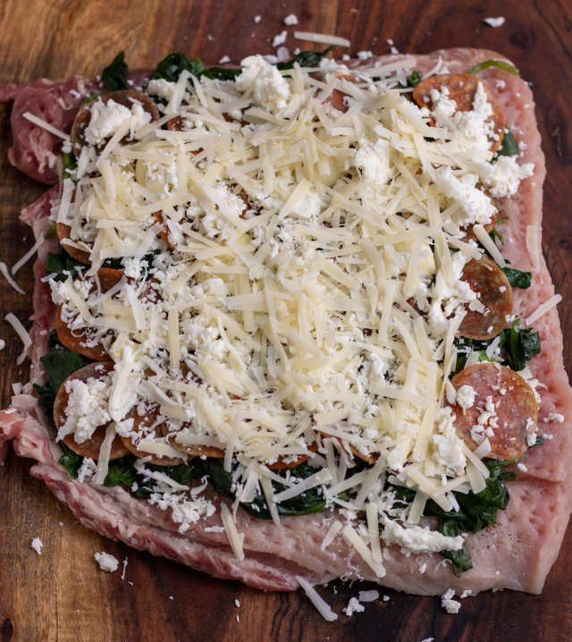 A wooden cutting board with a butterflied pork loin that's layered with spinach, pepperoni and cheese